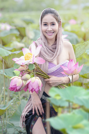 Young Beautiful Woman Relaxing With Lotus Flower Field,Asian Woman In Traditional Dress With Water Lily Flowers.