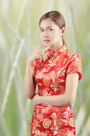 Asian woman in chinese dress traditional,beautiful women wear cheongsam and smile to you with chinese new year. Standard-Bild - 107496263