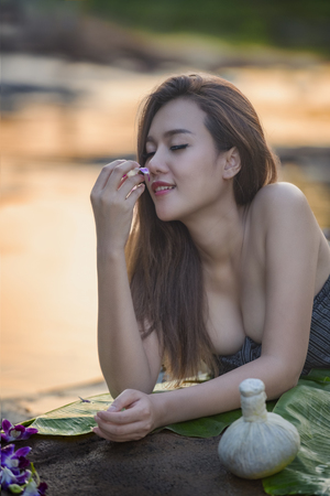 Beautiful Woman relaxing in round outdoor bath with tropical flowers,Skin And Body Care,Young Woman Getting Spa Treatment At Natural Spa,Spa Face Massage,Facial Beauty Treatment,Organic skin care