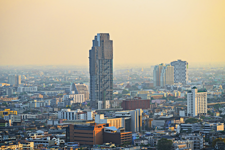 Bangkok Thailand Center and modern skyscraper city in misty gold lighting sunset air pollution in the city behind pollution haze. Фото со стока