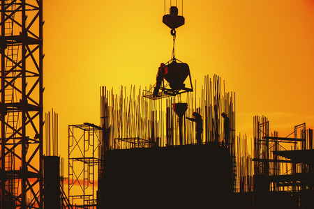 Engineer construction crews to work on construction site high ground heavy industry and safety concept,Silhouette teams of engineers controller at sunset background.