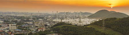 Aerial view of an industrial area with warehouses,Top view of warehouses, offices and buildings,Oil refinery with a background of the city.The factory is located in the middle of nature with sea view. Stock Photo