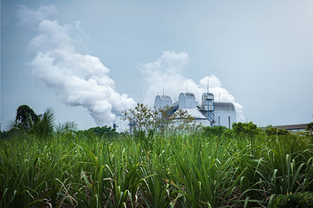Sugar cane factory,Toxic smoke from industrial plants,Smoking stack from lignite combined heat.Air pollution and climate change theme. Stock Photo