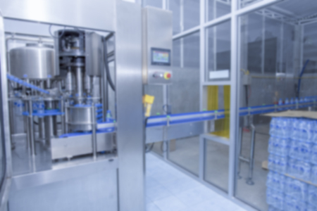 Blurred image of Modern Water filtration system and electronic control panel and tank at Water factory.Close Up of water bottles,water bottling line in equipment at the Water factory.