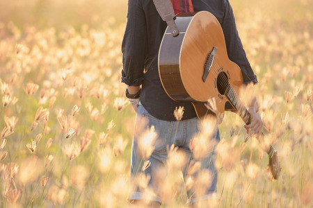Detail of a man playing guitar,musician playing acoustic guitar,concept for sunset over a misty meadow in summer evening and Flower nature dry field on sun background.
