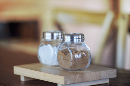 Sugar for coffee in a glass jar with a natural background.