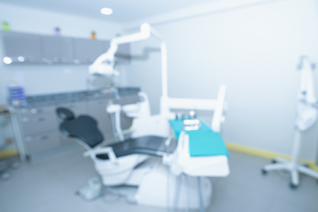 Blurred image of the dentist office, medical background.Dentist examining a patients teeth in the dentist. The concept of dental treatment in a dental clinic.