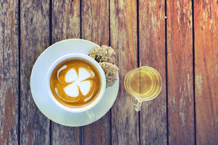Hot coffee on the old wooden table background,Cup of coffee with pattern on wooden background.