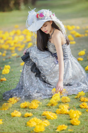 Young beautiful romantic woman in fashion dress taking a selfie in blooming garden with yellow flower.Outdoor fashion photo of beautiful young girl surrounded by flowers.Spring blossom.
