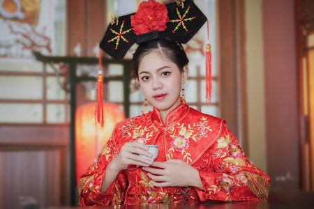 Asian beautiful young woman wearing traditional Chinese dress with attractive smile  on Chinese New Year.Chinese bride, wearing a traditional Chinese bride dress.