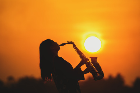 silhouette young woman playing the saxophone in sunset background.