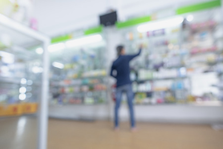 Pharmacy drugstore retail Interior blur background with healthcare product on medicine cabinet.Pharmacy interior with blurred background.Defocused image of medicines arranged in shelves at pharmacy.