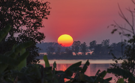 Beautiful Sunset with Big Sun in The River Or Lake,Reflection of Sky and The Big Sun,The river with Nightfall Landscape,Time lapse Majestic Sundown River or Sea View. Фото со стока