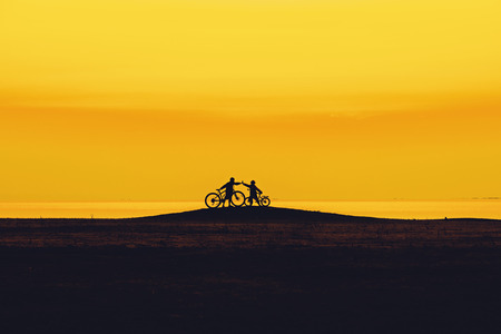 Children cycling on the beach.The team of miniature cyclists,Two children on the bikes, join hands together.Silhouette friend and bike relaxing on sunset background.Extreme sports concept for health.