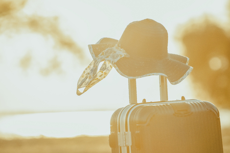 Tourist planning vacation with the help of world map with other travel accessories around.Suitcase and hat with background sunset.Travel concept nature of things ready to be taken on holiday. Фото со стока