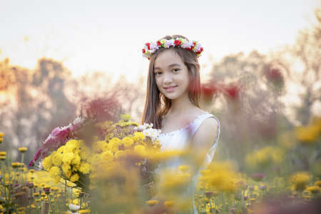 Beautiful girl in vintage dress and hat standing near colorful flowers.Beautiful romantic young woman of flowers posing on a background.Inspiration of spring and summer.Perfume.Art of romantic woman.