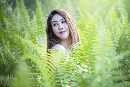 Portrait of young beautiful woman with perfect smooth skin in tropical leaves. woman in seasons spring leaves.  beautiful girl turning in green fresh summer gown. Enjoying the nature. Stockfoto
