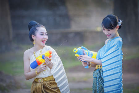 Thai girls and laos girls splashing water during Songkran festival,Water blessing ceremony of adults,Buddha statue water ceremony in songkran festival,Thailand traditional.