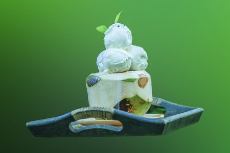 Fresh coconut milk ice cream on green background. Sweet Food and Dessert, Coconut Ice Cream in Coconut Shell.