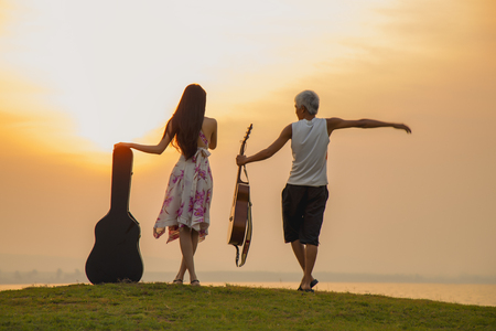 The teacher is teaching music in bright outfit, enjoying music at sunset. Full of joyful feeling satisfaction for beautiful young woman playing  the acoustic guitar in summer time vacation leisure. pretty lady lifestyle.
