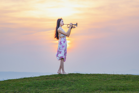 Beautiful woman in bright outfit, enjoying music at sunset. Full of joyful feeling satisfaction for beautiful young woman playing alone the violin in summer time vacation leisure. pretty lady lifestyle.