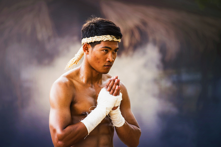 The fighter tying tape around his hand preparing to fight,Thai boxing at the river,Boxing fighters trainning outdoor,Muay Thai Stockfoto