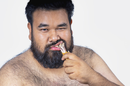 Fat men on a white background. Fat man with a big belly. Fat man eat a lot of food,Fat man eat fried chicken. extra weight, diet. Stockfoto