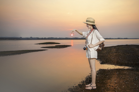 Traveler wear casual clothes relaxing at sunset on quiet lake.The lake most amazing tourist attractions.Sunset nature landscape.She reached out and picked up the sun that would disappear horizon.