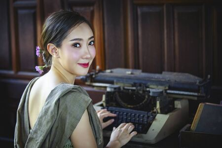 A beautiful Thai girl wearing a traditional Thai dress is using an old typewriter and looking at the camera. Retro typewriter placed on wooden planks.