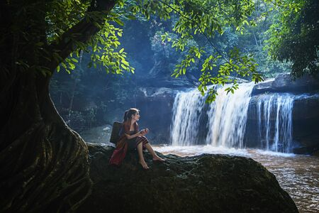 Beautiful girl with waterfall.  Young woman in front of waterfall. Woman relaxing in natural waterfall in natural park.