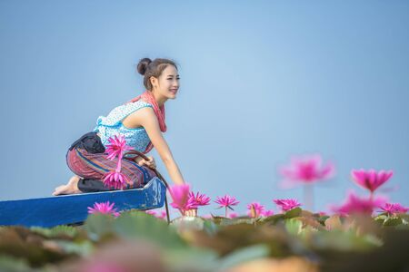 Picture of beautiful woman with lotus flower, Young beautiful woman relaxing with lotus flower, The girl holds the lotus flower in the field. 版權商用圖片