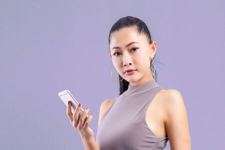 Woman working on laptop at office while talking on phone, Portrait of confident young woman working in her office with mobile phone. Working woman with colorful background. 版權商用圖片