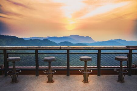 Old wooden chair with high sunrise view on the mountain And mild sunlight in the morning. Old wooden benches in the shady garden with area  view of the sunrise on the hilltop. Stockfoto
