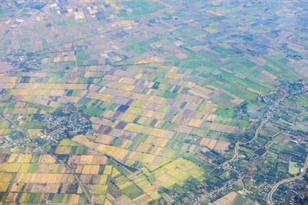 Aerial view of mountains, rivers, clouds, Agricultural Landscape areas the green and yellow rice field, Aerial view of grew in different pattern, And housing.Remote viewing. 版權商用圖片