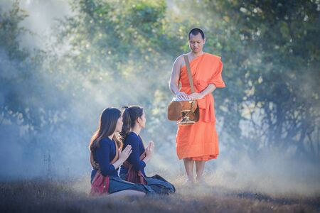 Young women make merit with monks Stock fotó