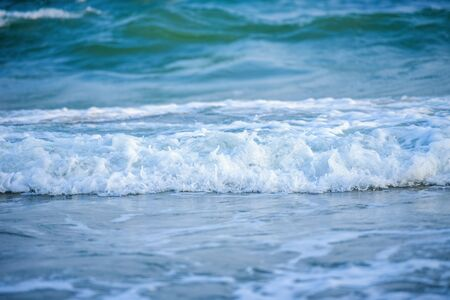 White wave of blue sea on sandy beach.View of a beach with breaking waves. Stok Fotoğraf