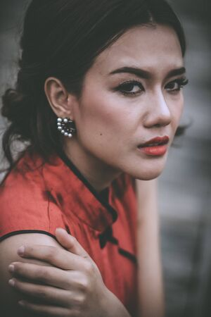 Close-up of young woman in Chinese dress with problems crying.