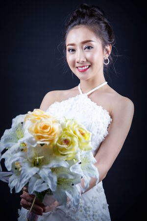 Portrait of a beautiful asian woman smiling brightly at the camera. Natural female in bride dress concept.