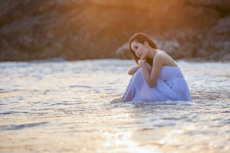 Beautiful young women are enjoying the beach side relaxation.A beautiful young girl enjoys the sea with waves and soft sunlight at sunset.