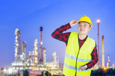 Young engineer with safety helmet with oil refinery industry plant background. Stock fotó