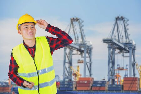 Young engineer with safety helmet with industrial port containers background.