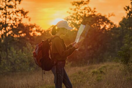 Hipster young Travelers with backpacks enjoying sunset at the mountain. Tourist traveler on background view sunset. Hiker looking map in nature travel trip.