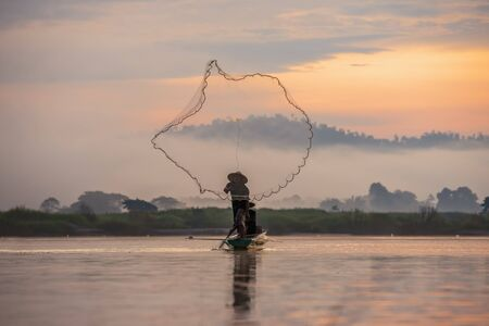Asian fishermen set sail for fishing on the Mekong River at sunrise.