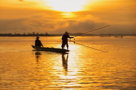 Asian fishermen set sail for fishing on the Mekong River at sunrise. Stok Fotoğraf - 132883684