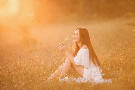 Beautiful woman wearing a white dress, happy with the meadow and sunset.