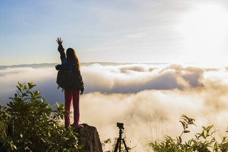 Tourists with fog on the top of the hill. Travelers breathe fresh air while photographing the beautiful sunrise and mist. Stok Fotoğraf