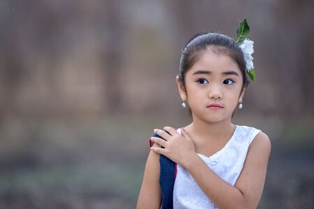 Happy Asian little girl in a traditional dress, Little girl in traditional Lanna costumes in Chiang Mai, Thailand.
