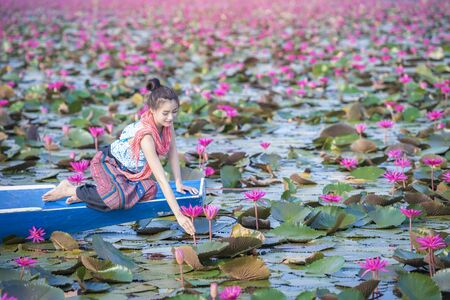 Red lotus sea, Woman in flower lotus lake, Beautiful Nature Landscape red Lotus sea in the morning with the bright day. Red Lotus Sea At Udon Thani ,Thailand. Stock fotó