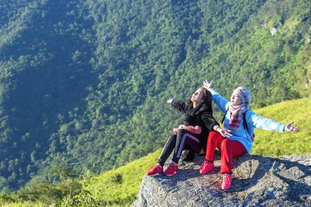 Freedom traveler enjoying a beautiful nature, Lifestyle concept. Young traveler on the top of mountain and enjoy the beauty of view. Young girl love wild life, travel, freedom.. Stock fotó