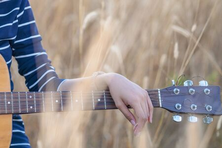 Guitar in the grass. Close up of a hand with a guitar in a brown meadow background. Banque d'images - 138734977